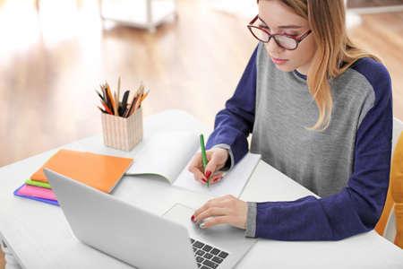 Ładny student z laptopem, studiując przy stole w pomieszczeniu