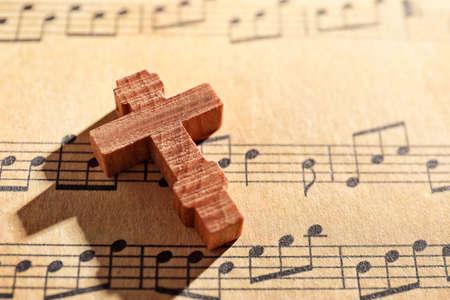 Wooden cross on music sheet
