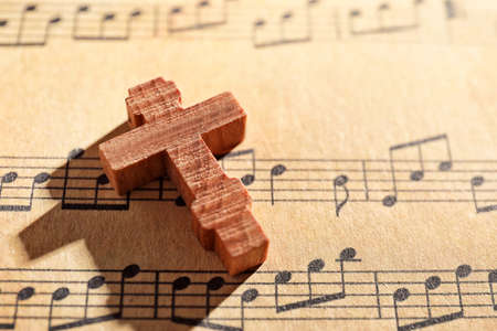 Wooden cross on music sheet
