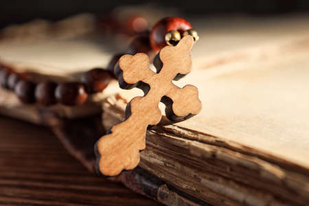 Rosary beads with wooden cross on old book, closeup