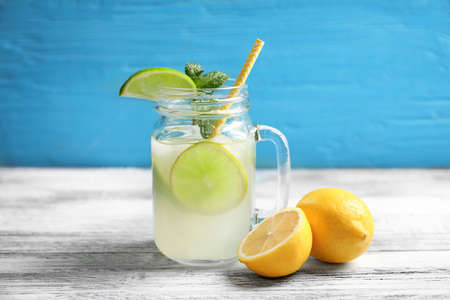 Tasty lemonade with lime and mint in mason jar on table