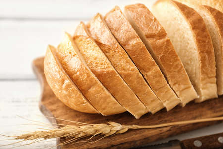 Wooden board with sliced bread on table