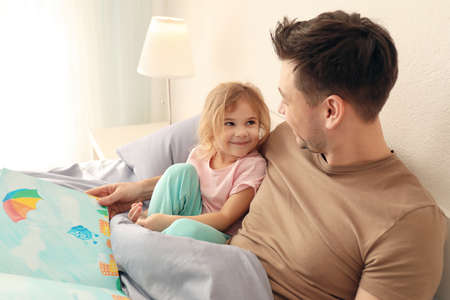 Father with little daughter reading bedtime story at home