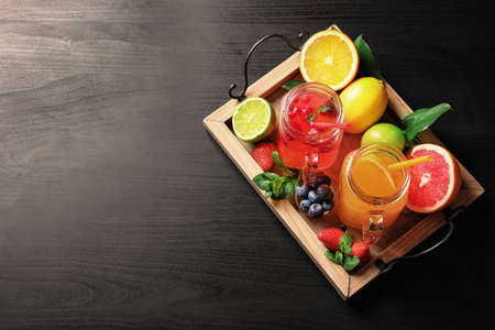 Tasty lemonades with berries and citrus fruits in mason jars on table