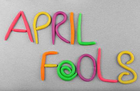 Phrase April fools made from plasticine on grey background