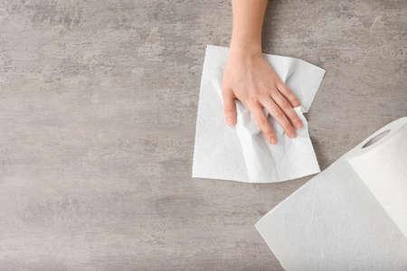 Frau wischt Tabelle mit Papiertuch