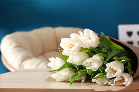 Bouquet of tulips on wooden table in living room
