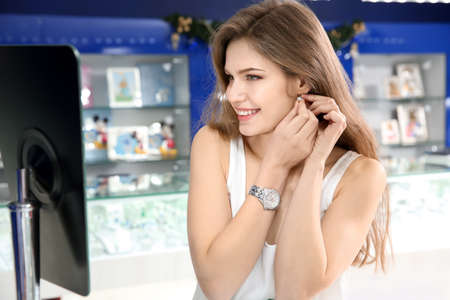 Young woman choosing earrings in jewelry store
