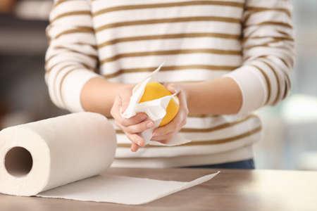 Vrouwen afvegende appel met keukenrol in keuken Stockfoto