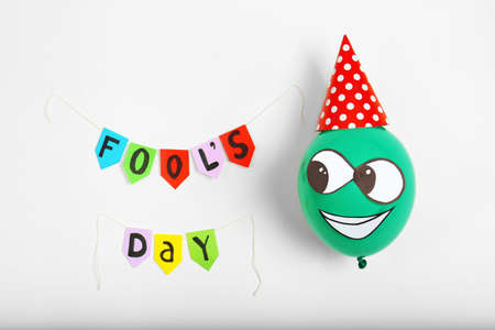 Colorful flags with phrase Fools day and funny balloon on light background. 1st April composition Stock Photo