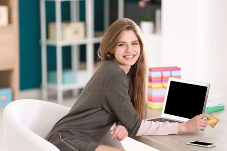 Young woman shopping online with credit card and laptop at table