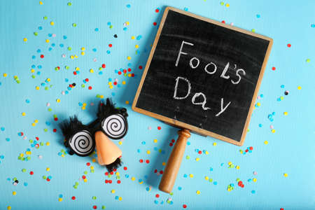 Chalkboard with phrase Fools day and funny glasses on color background. 1st April celebration Stock Photo