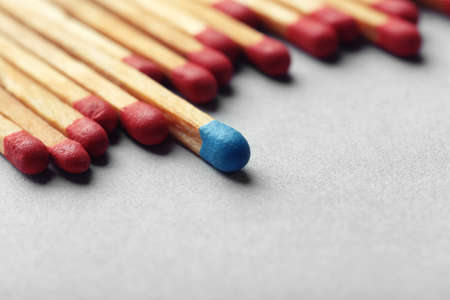 Blue match among red ones on light background. Difference and uniqueness concept Stock Photo