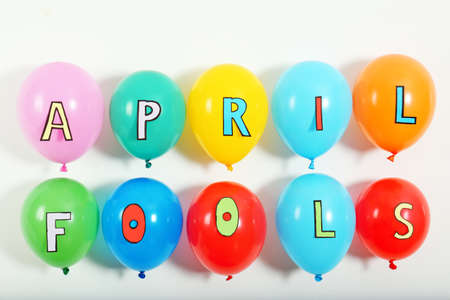 Colorful balloons with phrase April fools on light background Stock Photo