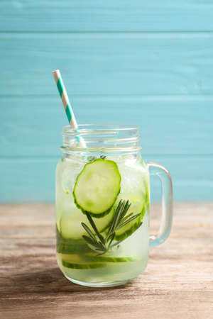Mason jar of fresh lemonade with cucumber on wooden table