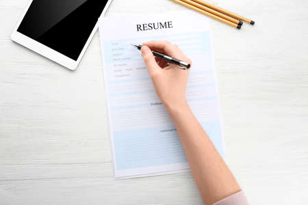 Woman filling in resume form at table. Job interview concept Stockfoto