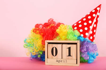 Block calendar and rainbow wig on table. April fools day celebration