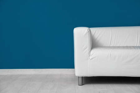 Comfortable sofa against color wall Stock Photo