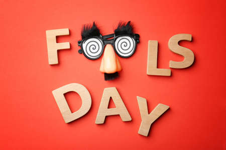 Phrase Fools day and funny glasses on color background. 1st April celebration