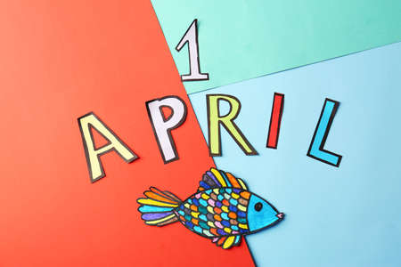 Phrase 1 April and paper fish on color background. Fools day celebration Stock Photo