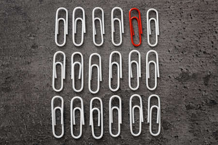 One red clip among white ones on gray background. Difference and uniqueness concept Stock Photo