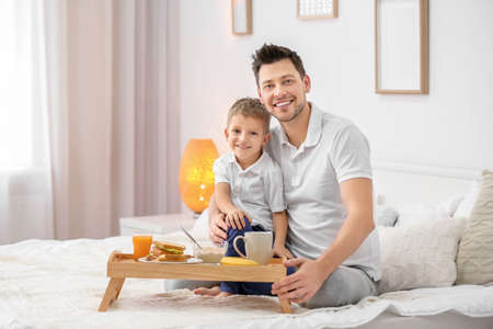 Father with son having breakfast in bed