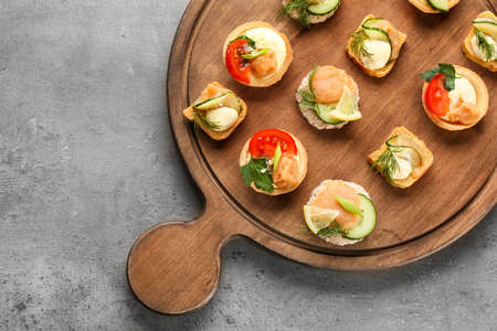 Tasty appetizers with codfish caviar on wooden board