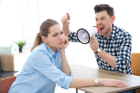 Angry boss with megaphone screaming at employee in office Stock Photo