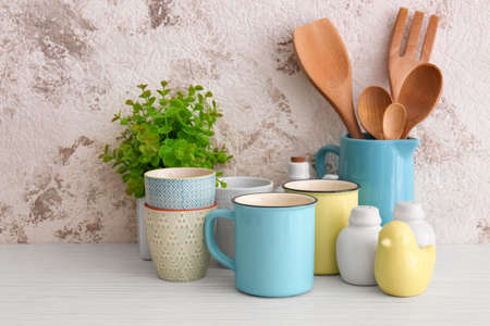 Cups and different cooking utensils on table