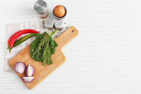 Cutting board and products on light background. Cooking utensils