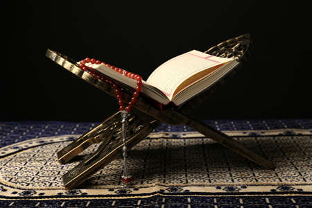 Open holy book of Muslims with prayer beads on stand