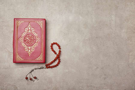 Holy book of Muslims and prayer beads on gray background