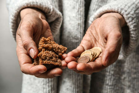 Poor woman holding piece of bread and coins, closeup