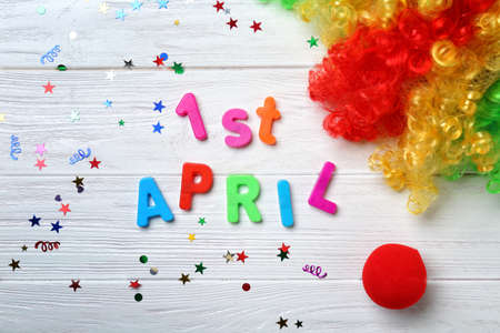 Phrase 1st April, clown nose and rainbow wig on wooden background. Fools day celebration