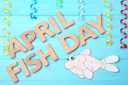 Paper fish and phrase April fish day on color background Stock Photo