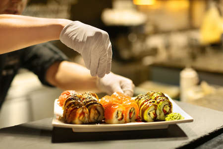 Male chef preparing sushi rolls for serving in restaurant