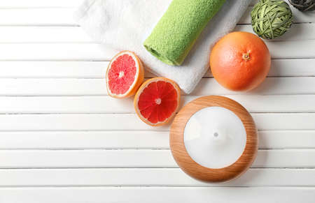 Essential oil diffuser and grapefruit on table