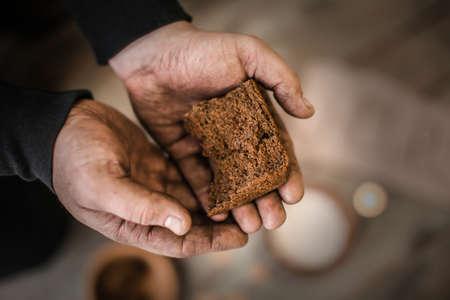 Poor man holding bread, closeup Stock Photo