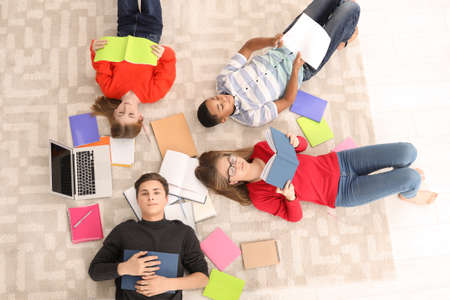 Group of teenagers doing homework on floor