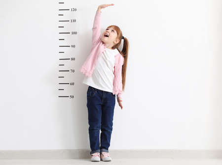 Little girl measuring height near white wall Stockfoto