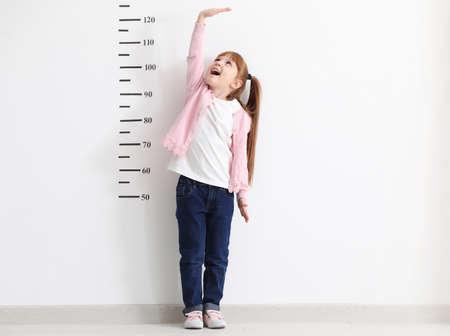 Little girl measuring height near white wall