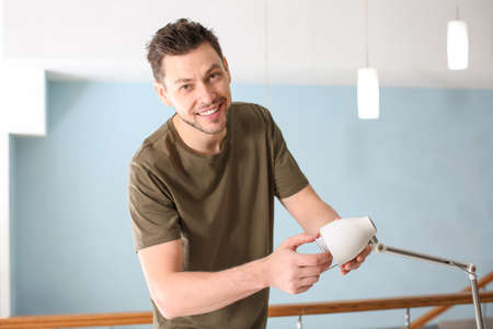 Man changing light bulb in lamp at home Stock Photo