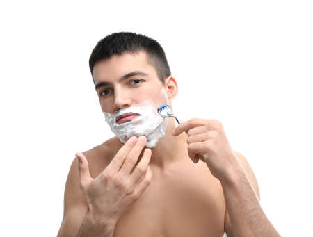 Handsome young man shaving against white background