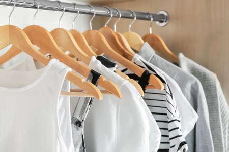 Wieszaki z różnymi ubraniami w szafie garderoby