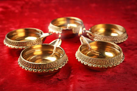 Diwali diyas or clay lamps on red fabric