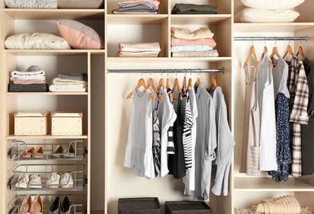 Duża szafa wnękowa z różnymi ubraniami i butami