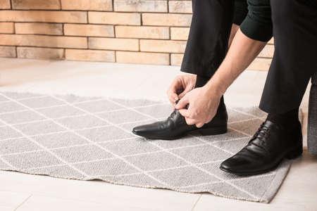 Man tying shoelaces indoors 写真素材
