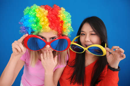 Young women in funny disguise posing on color background. April fool's day celebration