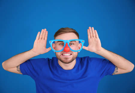 Young man in funny disguise posing on color background. April fools day celebration Stock Photo