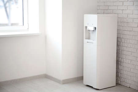 Modern water cooler near brick wall